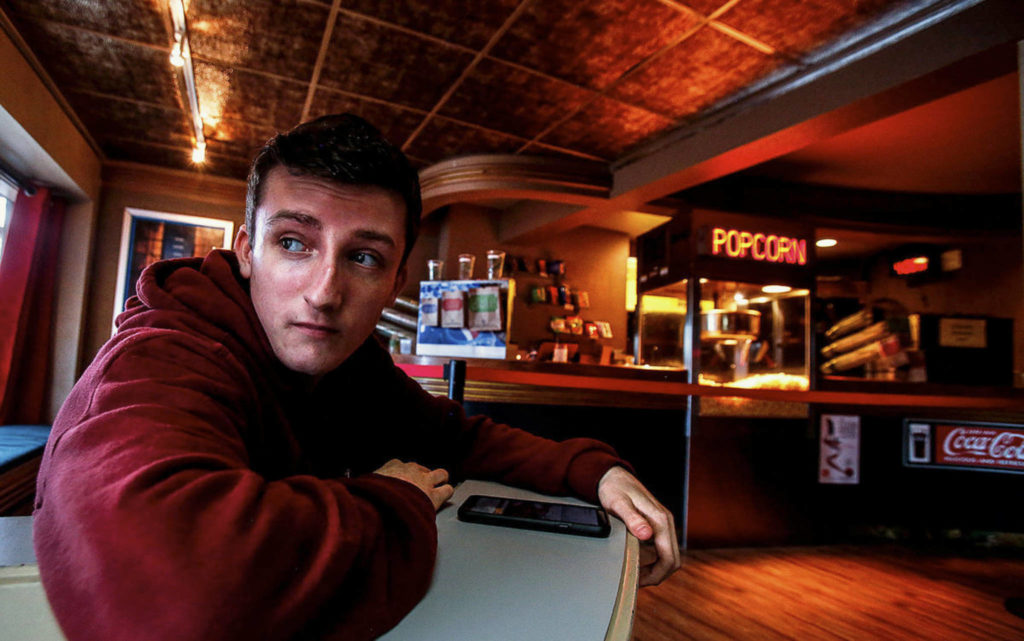 From the Edmonds Theater's distinctive Art Deco lobby, employee Jack Eccleshall, 18, glances out the window. (Dan Bates / The Herald)