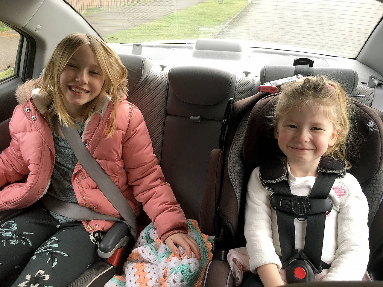 Evelyn Renner, 9, and Hazel Renner, 4, sit in their booster and child car seats, respectively. Updated requirements to Washington's child car restraint law now specifiy that a child younger than 13 who is not 4 feet, 9 inches, must use a booster seat. (Lena Renner)