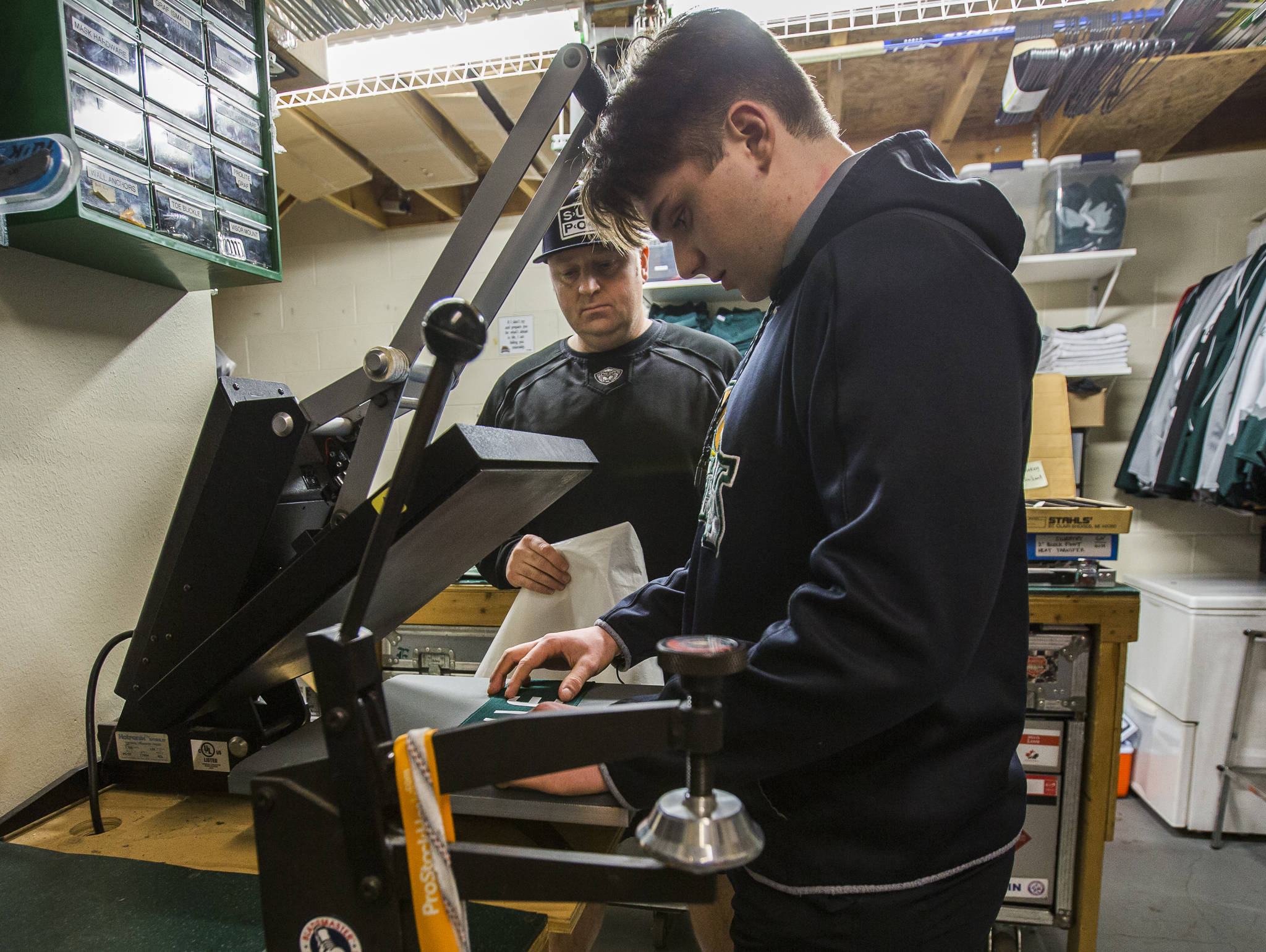 Everett Silvertips equipment manager James Stucky (rear) and his son, C.J. Stucky work on the nameplate for a new member of the team on Jan. 7 at Angel of the Winds Arena in Everett. C.J. Stucky plays for the Jr. Silvertips 18U team. (Olivia Vanni / The Herald).