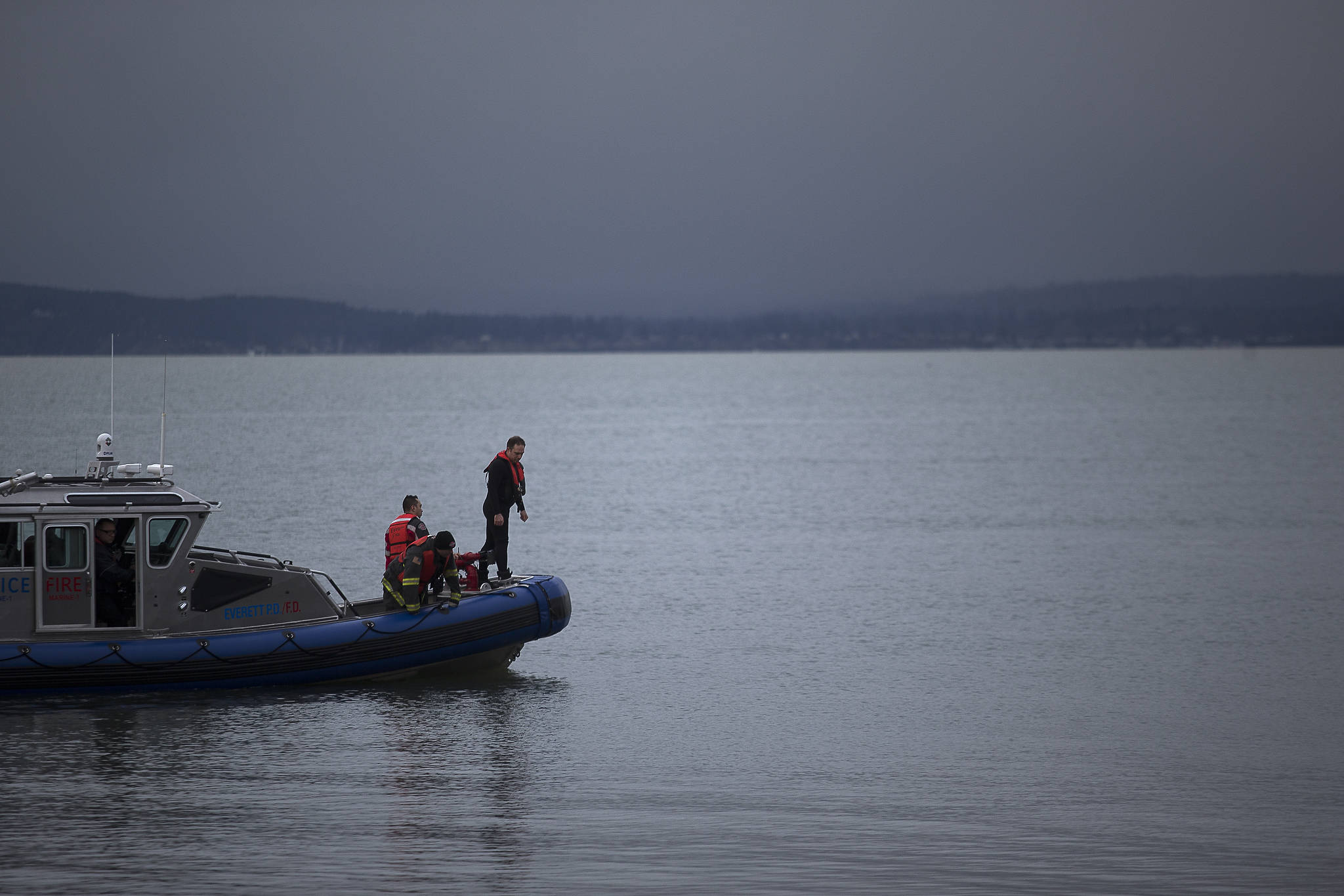 Everett rescue personnel peer over the sides of a boat in search of a man who was last seen swimming to shore after his inflatable boat capsized off the beach north of the Mukilteo ferry Wednesday. (Andy Bronson / The Herald)
