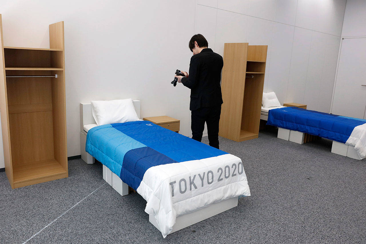 A journalist films a cardboard bed in a display room showing furniture for the Tokyo 2020 Olympic and Paralympic Villages. (AP Photo/Jae C. Hong)