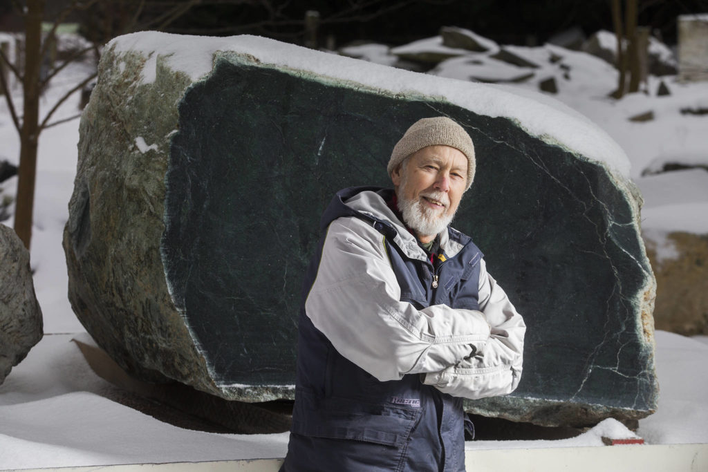 Arlington prospector Ed Molsee stands in front of a 16,000-pound jade boulder, he and fellow prospector Jason Henry, of Marblemount, discovered in the Darrington area. (Andy Bronson / The Herald)