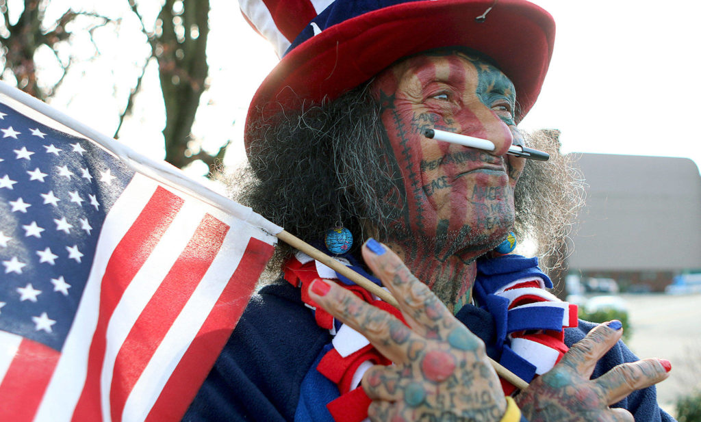 Samiu Bloomfield, seen here in March 2016, stands on Broadway in Everett looking like a feral version of Uncle Sam as he waves to people. He died Sunday at 70 years old. (Kevin Clark / Herald file)