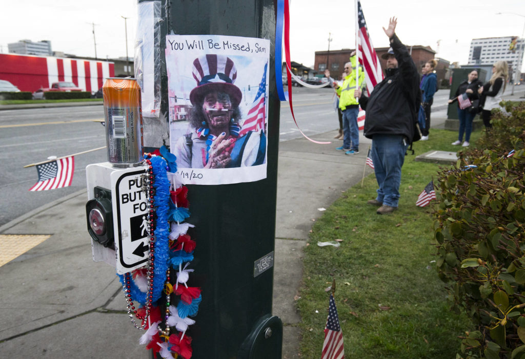 A photo of Samiu Bloomfield is taped to a pole where his friends and fans gather on Broadway to wave in his honor Monday in Everett. (Andy Bronson / The Herald)