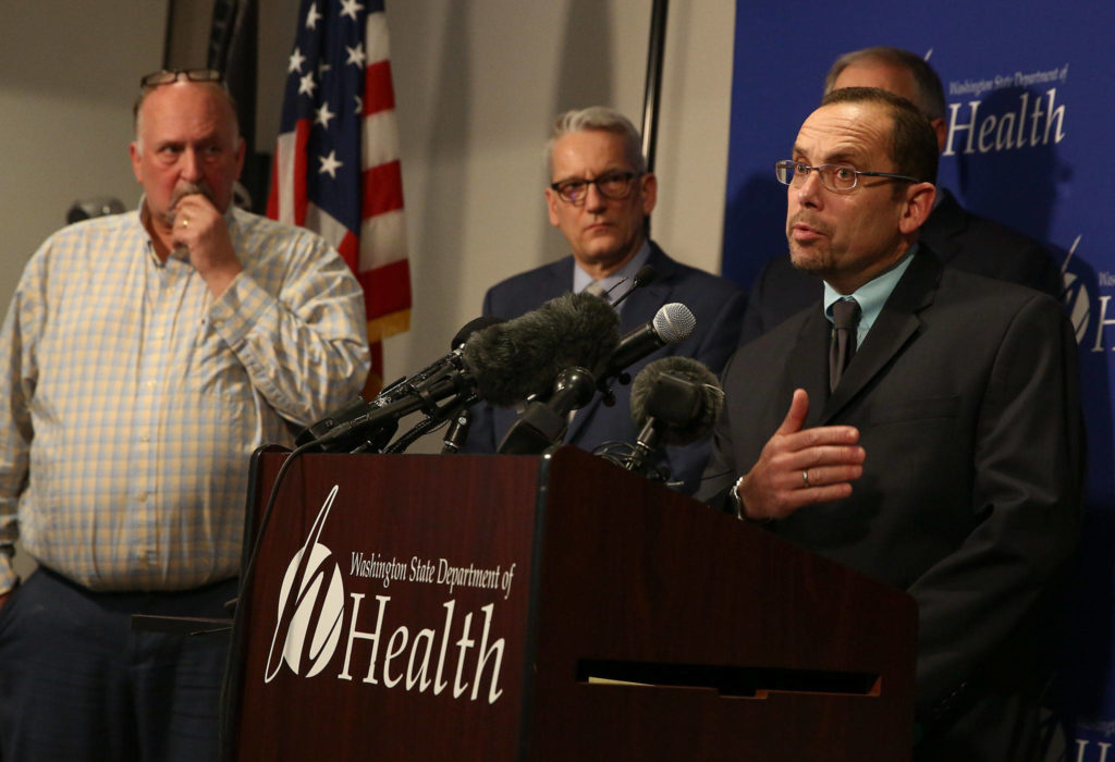 Dr. Chris Spitters (right), interim health officer for the Snohomish Health District, fields questions during a news conference Tuesday afternoon at the state Public Health Laboratories in Shoreline. (Kevin Clark / The Herald)