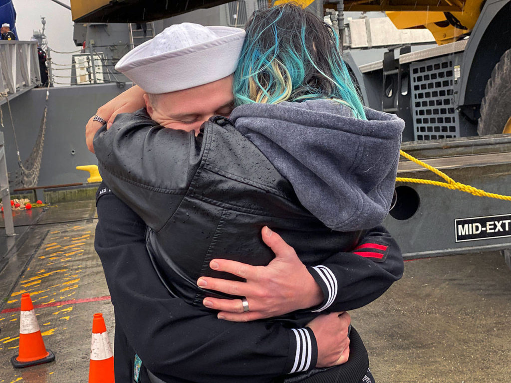 A sailor gets a big hug at the arrival of the USS Gridley at Naval Station Everett on Tuesday morning. (Sue Misao / The Herald)