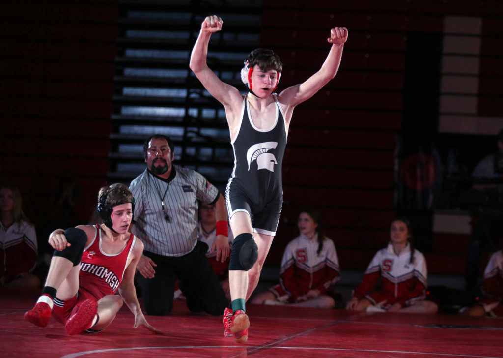 Stanwood's Bryan Roodzant raises his arms in victory after pinning Snohomish's Colby Skowron as Snohomish lost to Stanwood 41-39 in a boys' wrestling meet on Tuesday, Jan. 28, 2020 in Snohomish, Wash. (Andy Bronson / The Herald)