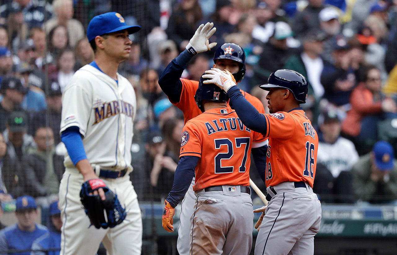 Seattle Mariners starting pitcher Marco Gonzales (left) heads back to the mound as Houston Astros' Jose Altuve (27) and Tony Kemp (18) celebrate scoring with Carlos Correa in the sixth inning of a baseball game Sunday, April 14, 2019, in Seattle. (AP Photo/Elaine Thompson)