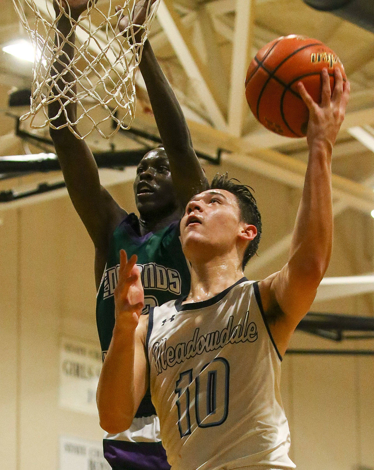 Meadowdale's Colton Walsh (10) attempts a layup with Edmonds-Woodway's Nuer Bol defending Friday evening at Meadowdale High School in Lynnwood. Meadowdale won 64-53. (Kevin Clark / The Herald)