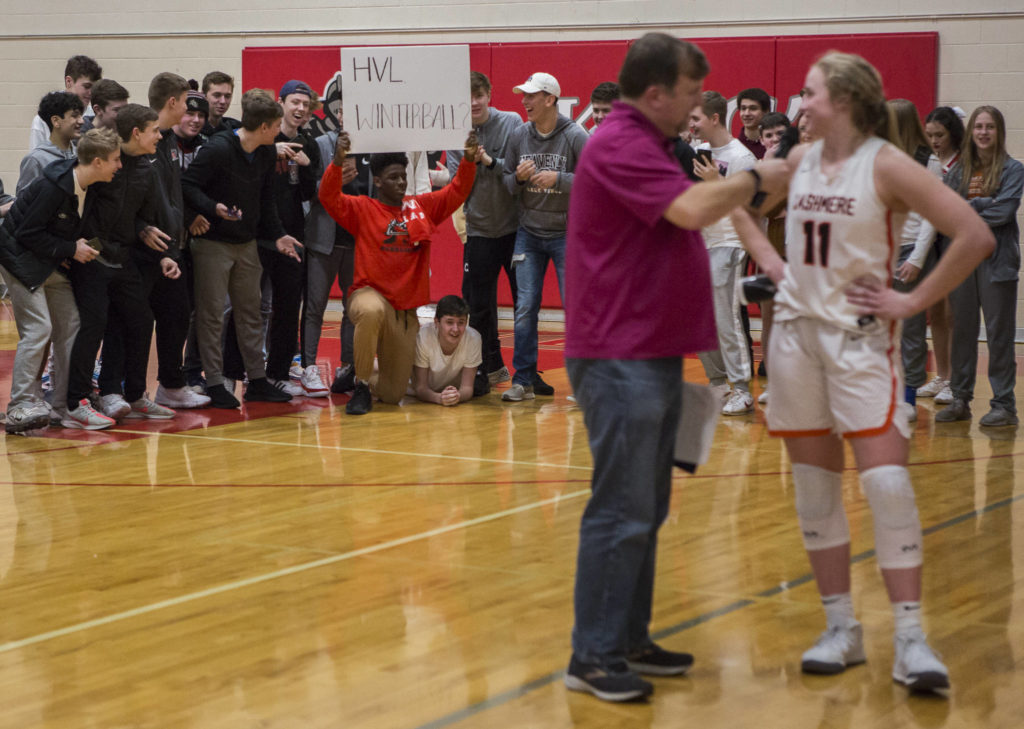 Cashmere's Hailey Van Lith smiles as she looks back and sees a King's student with a sign asking her to their Winterball dance after a game on Saturday in Shoreline. (Olivia Vanni / The Herald)