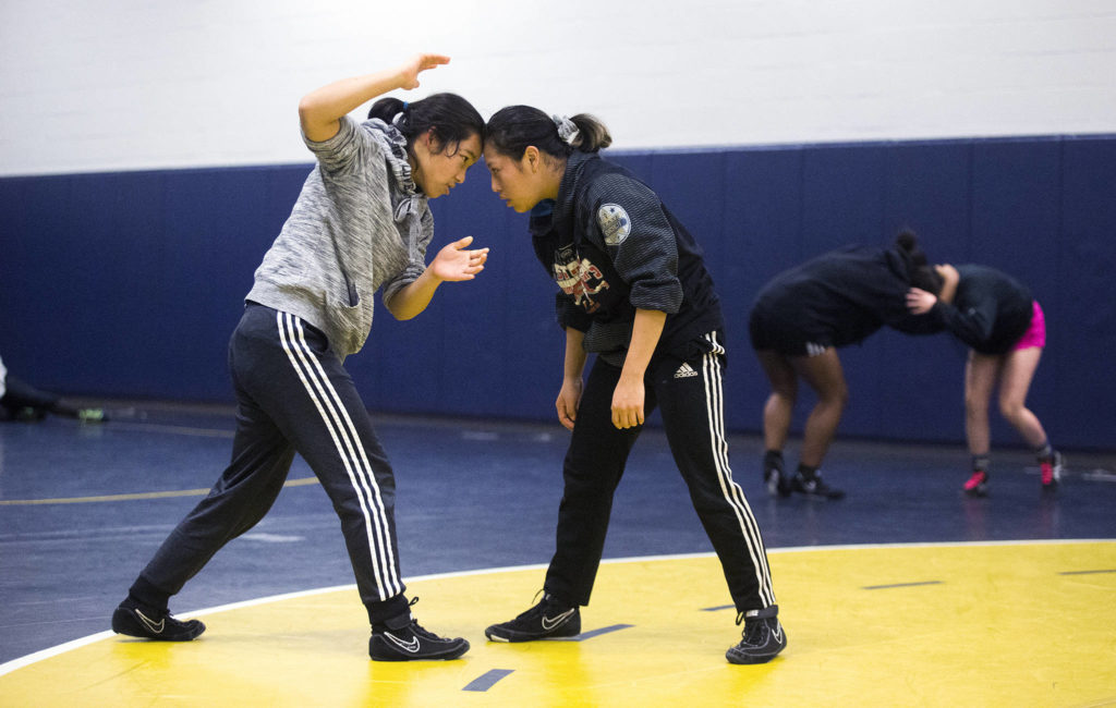 Everett's Sumina Gurung (left) works with teammate Craydi Moen during wrestling practice on Monday in Everett. Gurung is a sophomore born in Nepal and Moen, a senior, was born in Mexico and moved to America at around age 8. (Andy Bronson / The Herald)