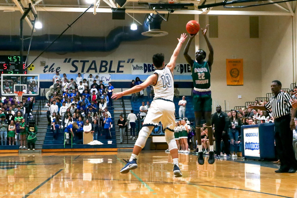 Edmonds-Woodway's Mutdung Bol attempts a 3-pointer with Meadowdale's Colton Walsh defending Friday evening at Meadowdale High School in Lynnwood January 24, 2019. (Kevin Clark / The Herald)