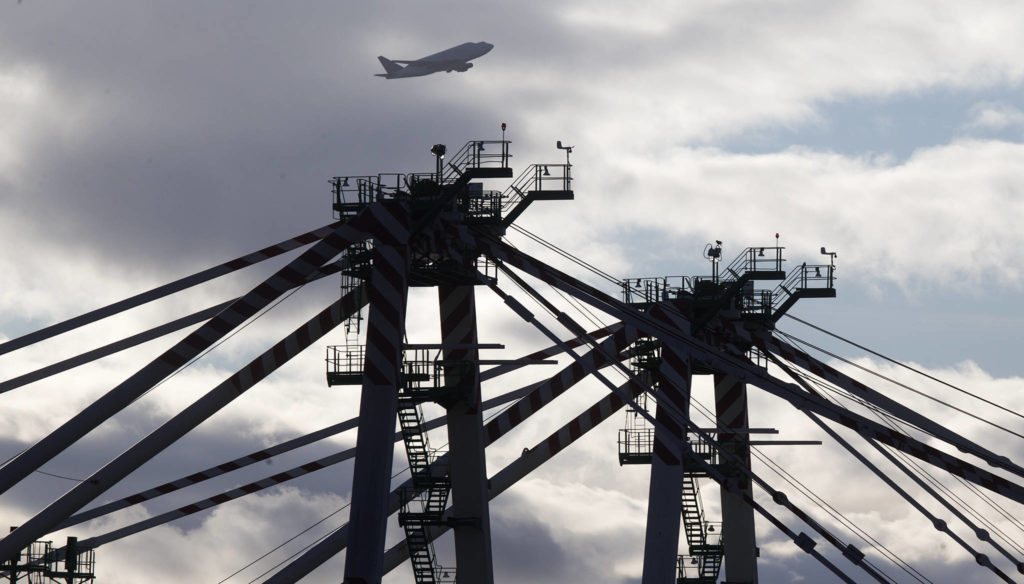 A Boeing Dreamlifter plane flies over the two new cranes Monday at the Port of Everett South Terminal in Everett. At 215-feet tall, the cranes are required to have FAA-approved markings or lighting. (Andy Bronson / The Herald)