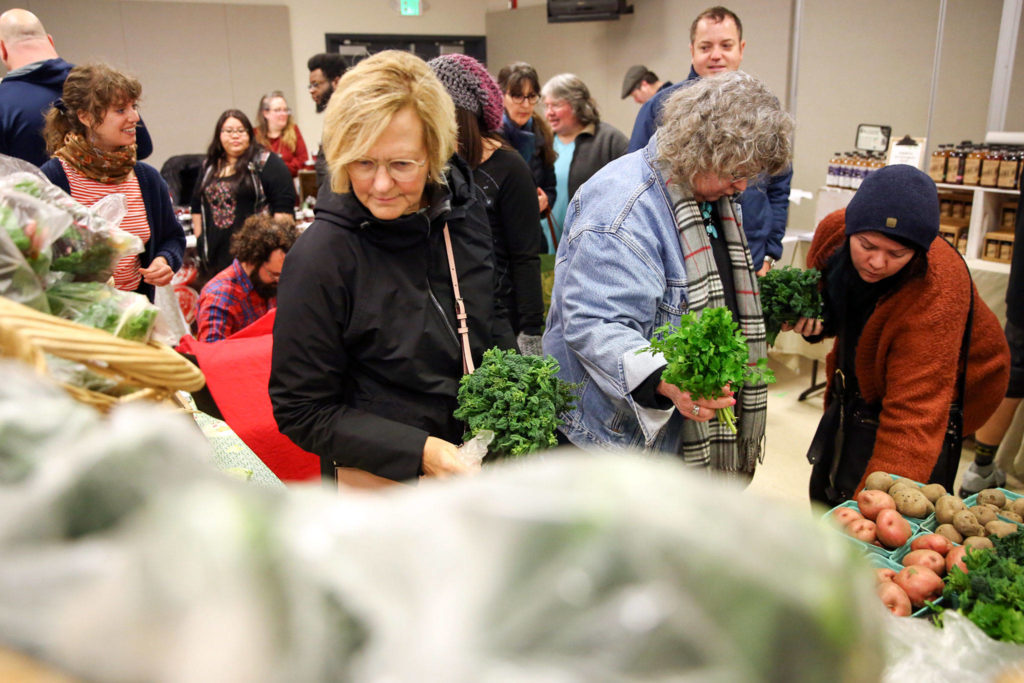 Markets goers browse produce Sunday morning at the Popup Market at Village Theatre in Everett on February 9, 2020. (Kevin Clark / The Herald)