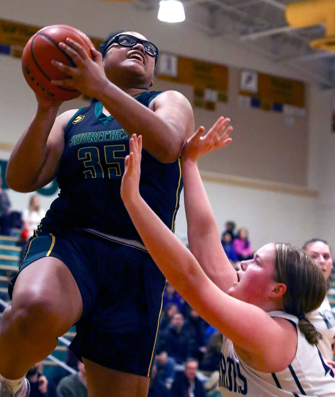 Shorecrest center Kiana Lino attempts a shot over Edmonds-Woodway's Halle Waram during the Scots' 59-52 overtime win Tuesday night. Lino hit a key 3-pointer in overtime and finished with 15 points and 15 rebounds. (Kevin Clark / The Herald)