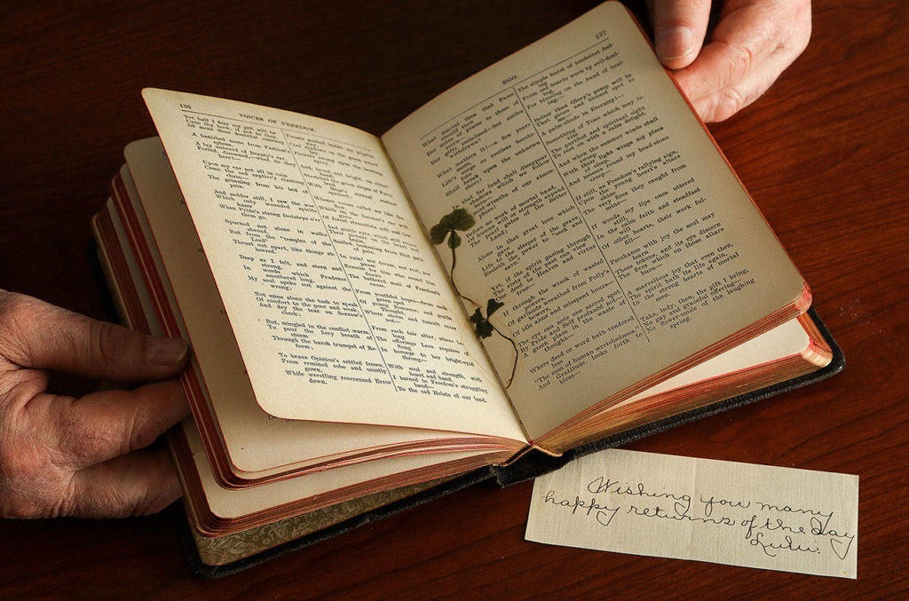 Phil Jubie holds a poetry book that once belonged to his great-uncle, Edwin Ritchie. With the book, a gift to Ritchie in 1906, are pressed four-leaf clovers and a sweet message from someone named Lulu. (Dan Bates / The Herald)