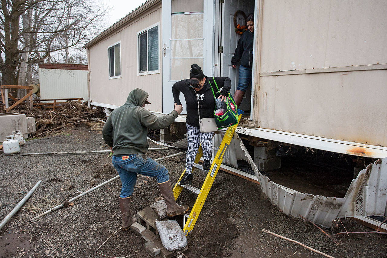 In this Feb. 8 photo, resident Patty Haid is helped from her flood-damaged home in Pendleton, Oregon. (Ben Lonergan/East Oregonian via AP)