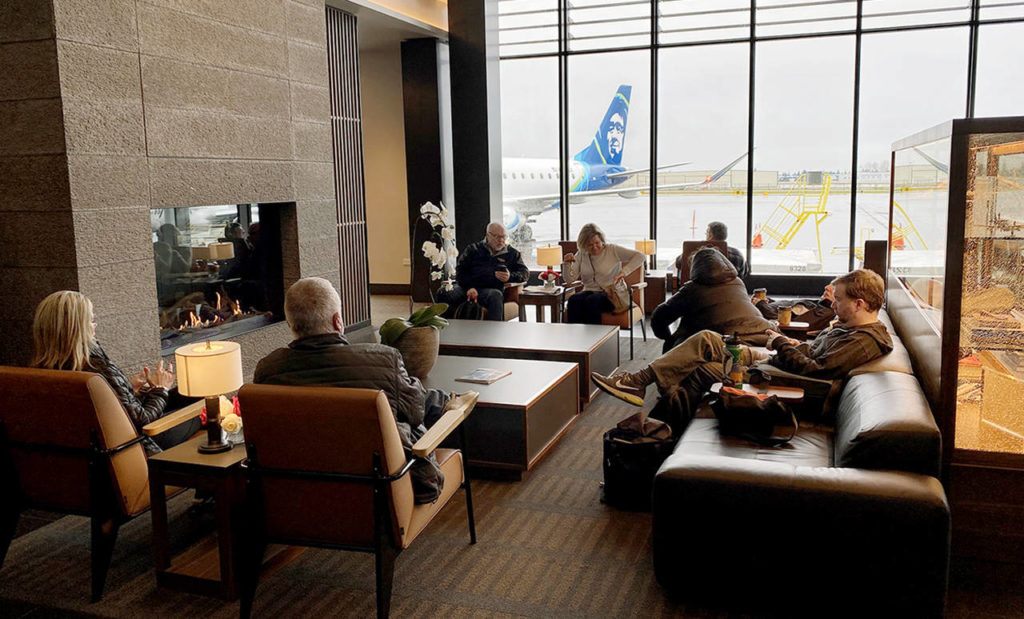 People wait for their flights in the fireplace lounge at Paine Field airport Thursday morning. (Sue Misao / The Herald)
