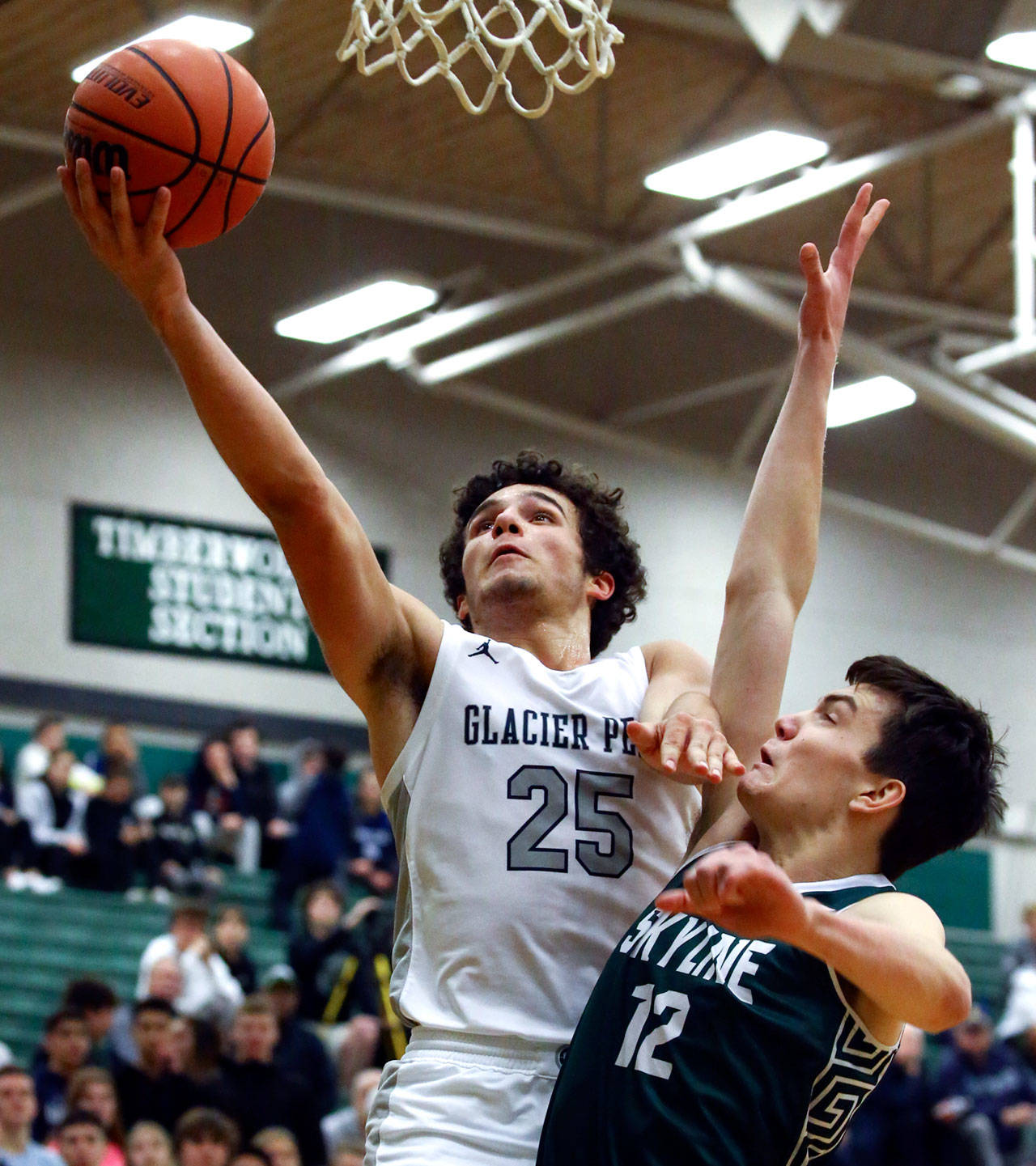 Glacier Peak's Brayden Quantrille (25) drives for a layup with Skyline's Zach Ulmer trailing during a Wes-King Bi-District Tournament game Tuesday evening at Jackson High School in Mill Creek. (Kevin Clark / The Herald)