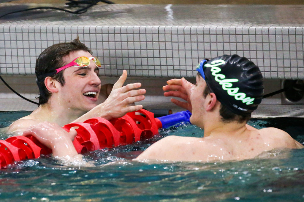 Glacier Peak's Matthew King celebrates with Jensen Elsemore of Jackson at the end of 100-yard freestyle during the 4A NW District Swim Meet on Feb. 15, 2020, at the Snohomish Aquatic Center. (Kevin Clark / The Herald)