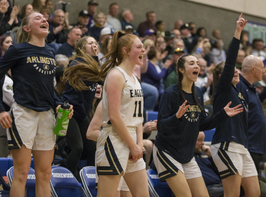 The Arlington bench reacts to a teammate making a 3-point shot during a 3A state regional game against Lake Washington on Saturday in Shoreline. (Olivia Vanni / The Herald)