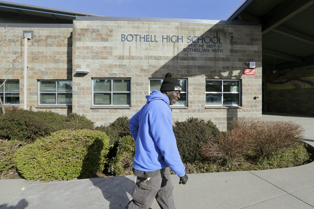 A school janitor opens the door to a staff room inside Bothell High School, which was closed for the day, on Thursday. The school was closed after a staffer's family member was placed in quarantine for showing symptoms of possibly contracting coronavirus. (Elaine Thompson / Associated Press)