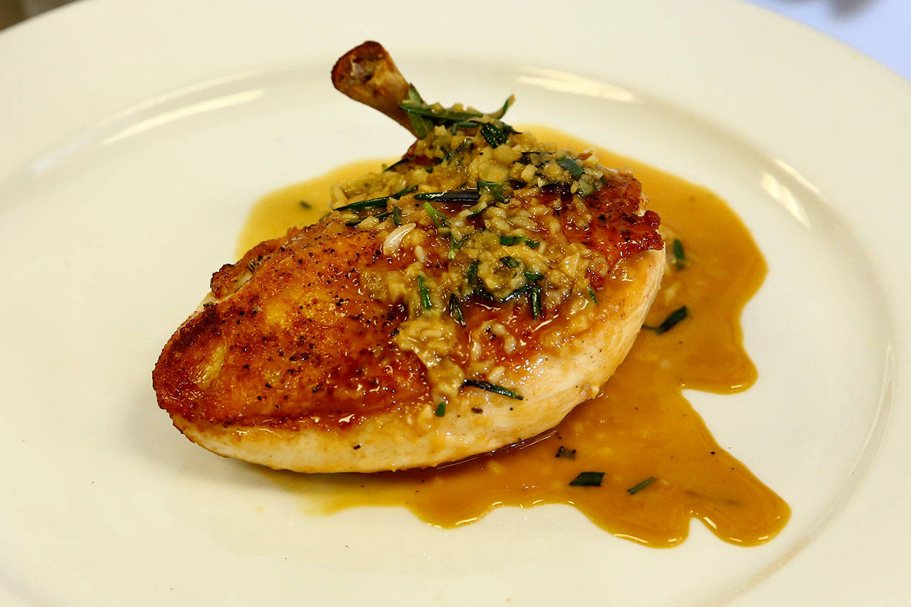 "Russell's pan-seared chicken breast with rosemary-garlic sauce features an ""airline"" cut breast, meaning the wing bone is still attached. (Kevin Clark / The Herald)"
