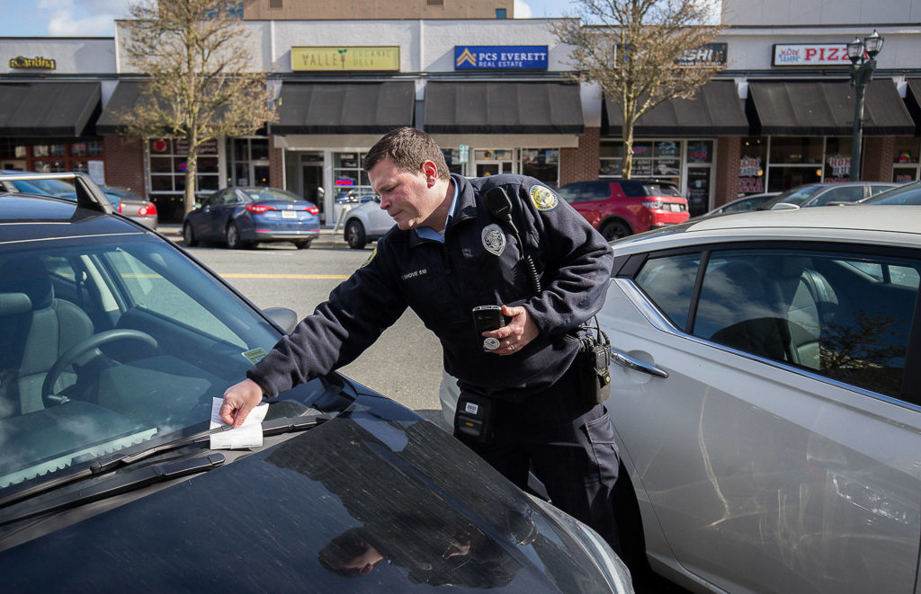 Everett parking enforcement officer Donny Shove puts a ticket on a vehicle for parking over 90 minutes on Colby Avenue on Wednesday in Everett. (Andy Bronson / The Herald)