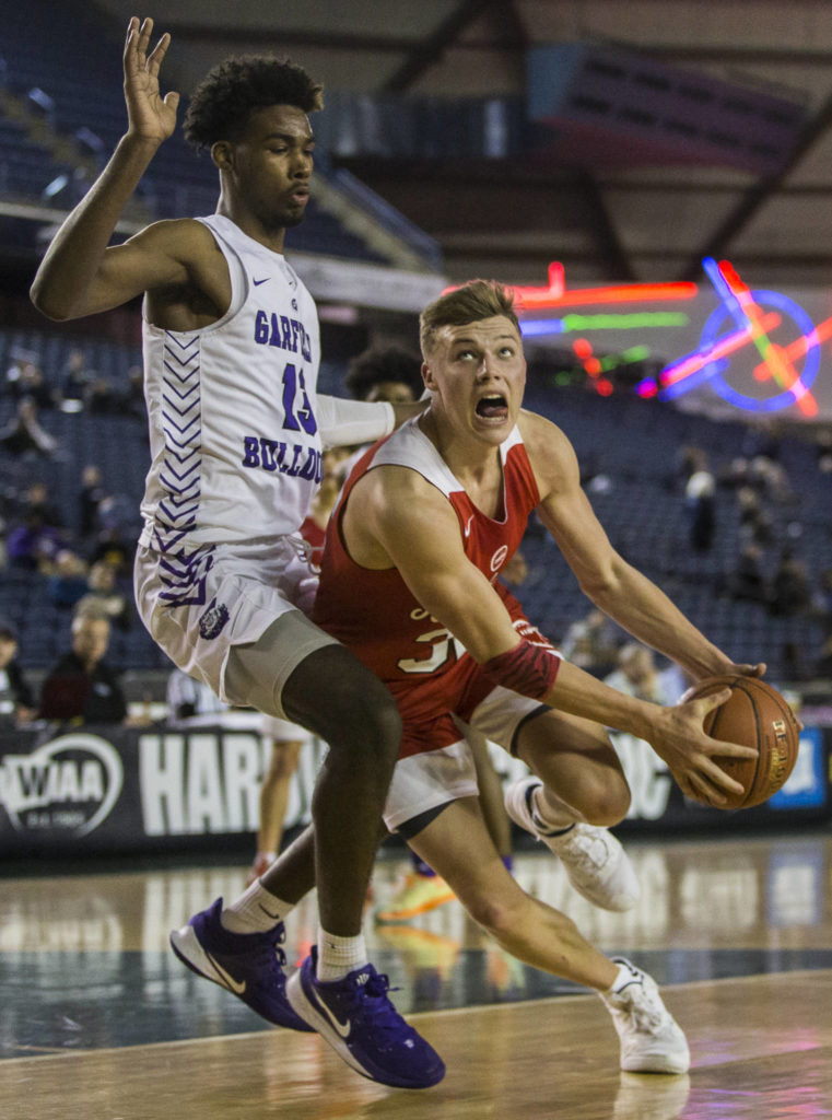 Marysville Pilchuck's Aaron Kalab (right) drives to the hoop while being guarded by Garfield's Tari Eason during a 3A boys Hardwood Classic quarterfinal on Thursday in Tacoma. (Olivia Vanni / The Herald)