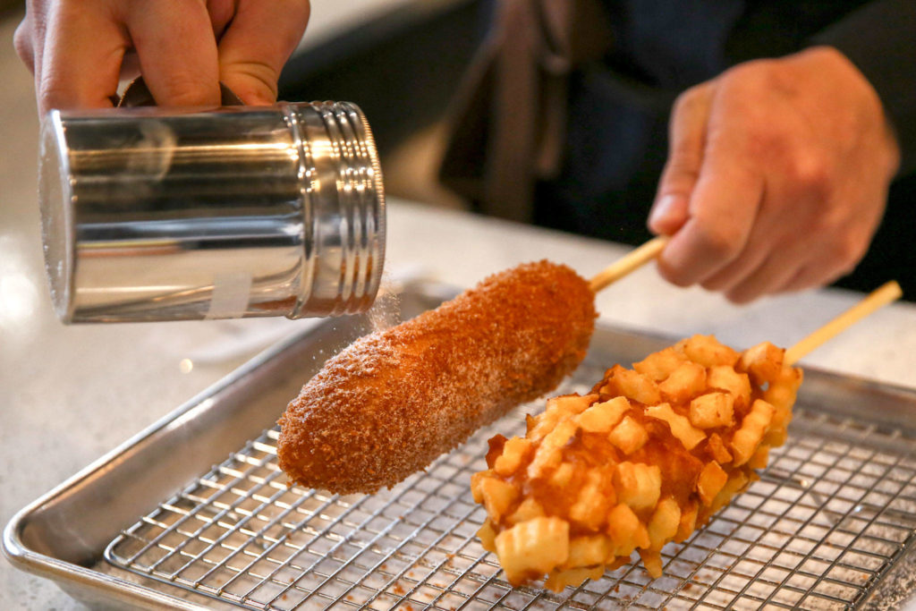 Co-owner Sean Lee sprinkles sugar on corn dogs at Seoul Hotdog in Lynnwood. (Kevin Clark / The Herald)