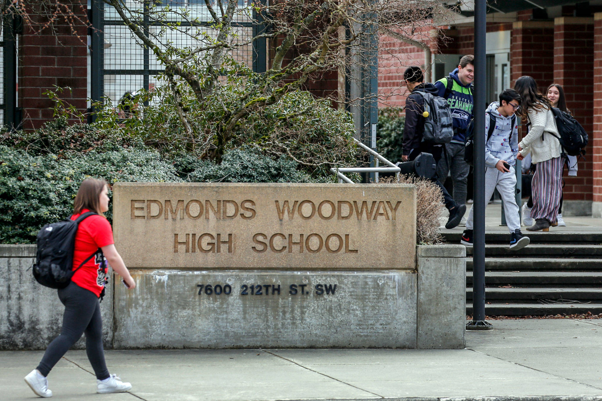 Students make their way after school at Edmonds-Woodway High School on Thursday. All public and private schools in Snohomish, King and Pierce counties must close for six weeks. (Kevin Clark / The Herald)