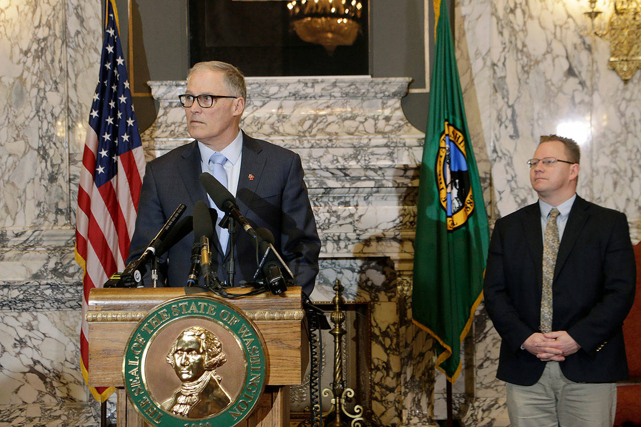 Washington Gov. Jay Inslee (left) is joined by Superintendent of Public Instruction Chris Reykdal on Friday as he discusses the expansion of school closures and prohibition of large gatherings across all of Washington in an effort to slow the spread of the new coronavirus. (AP Photo/Rachel La Corte)