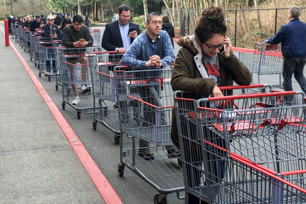 Customers wait in a line wrapped around the building Tuesday morning at Costco in Everett on March 17, 2020. The wholesale retailer was only allowing 30 people in at a time. (Kevin Clark / The Herald)
