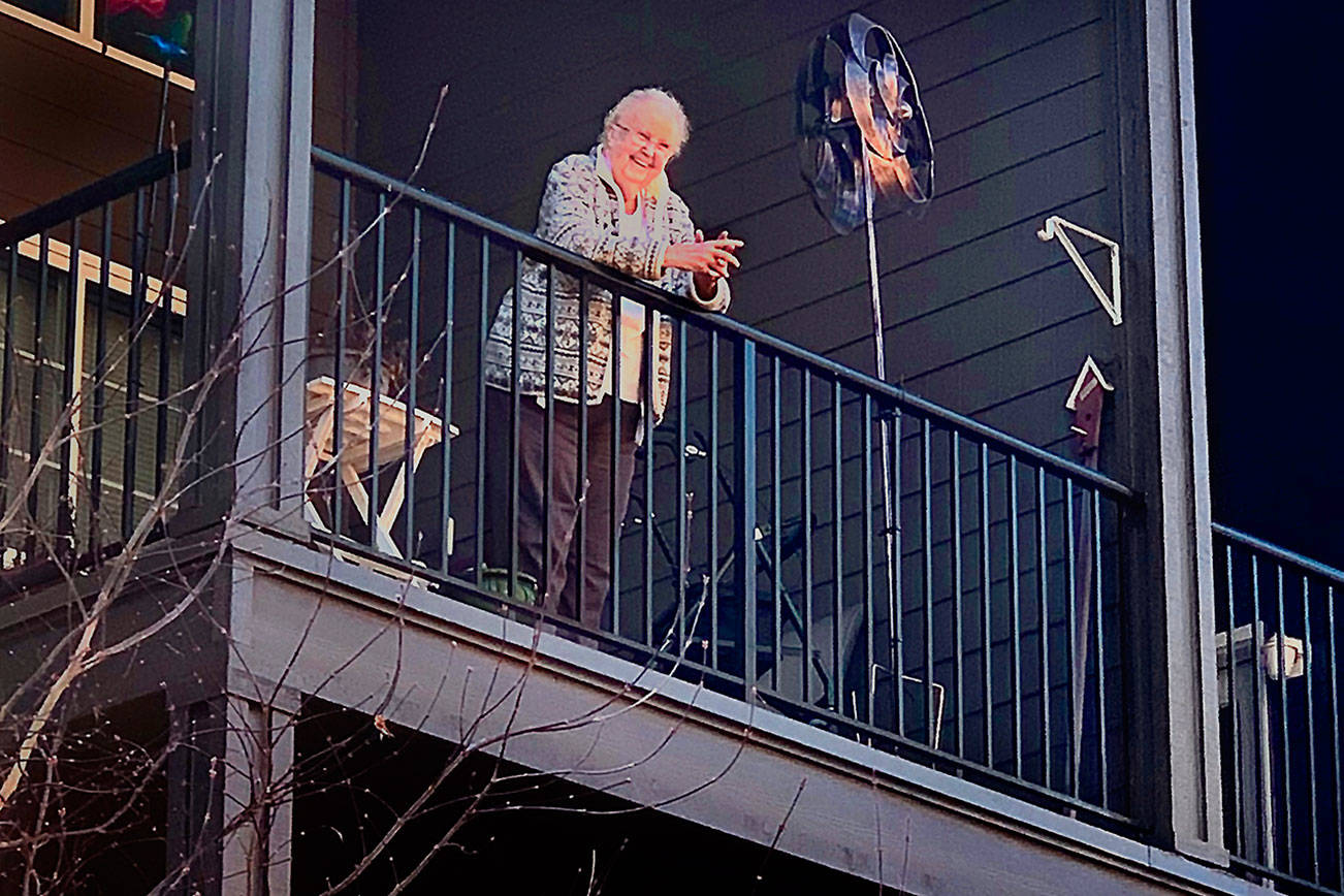 "Carolyn Ross, on the balcony of her apartment at Arlington's Olympic Place, is happily surprised on her 96th birthday Monday. Unable to visit the senior community due to coronavirus precautions, her children and their spouses sang ""Happy Birthday"" from outside. (Vanessa Ross photo)"