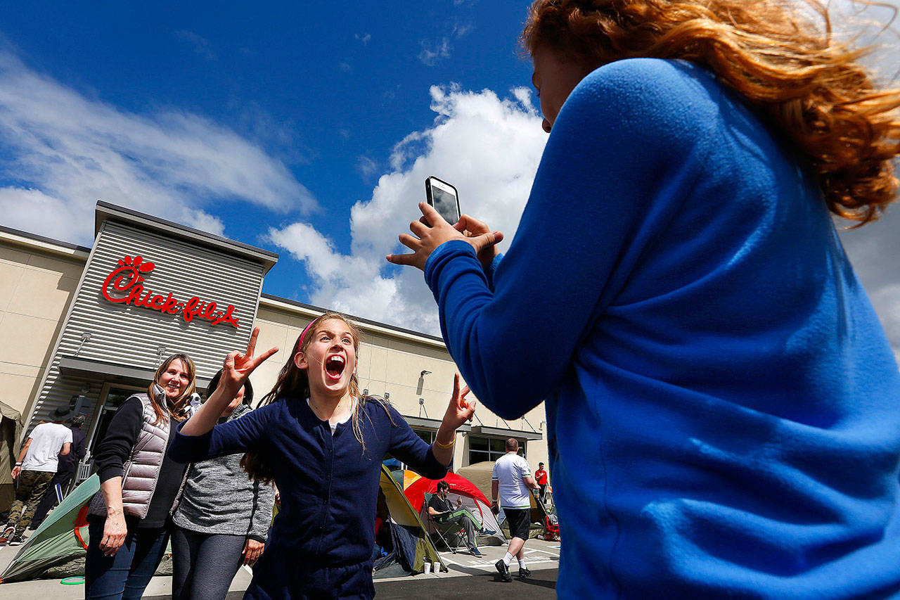 Chloe Charles (center) jumps into the middle of a picture being taken by Jada Summers of the girls' respective mothers, Renee Charles (left) and Debbie Summers, outside a Chick-Fil-A in Lynnwood in May 2015. (Mark Mulligan / Herald File)