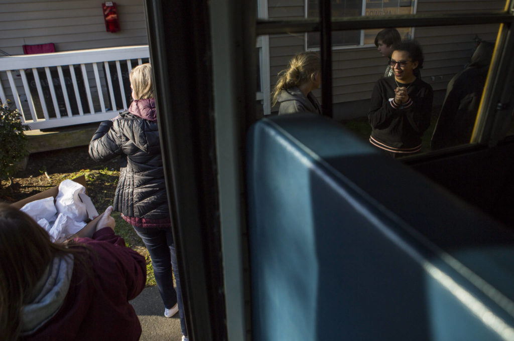 Children lineup next to the bus to receive their meals on Wednesday in Marysville. (Olivia Vanni / The Herald)