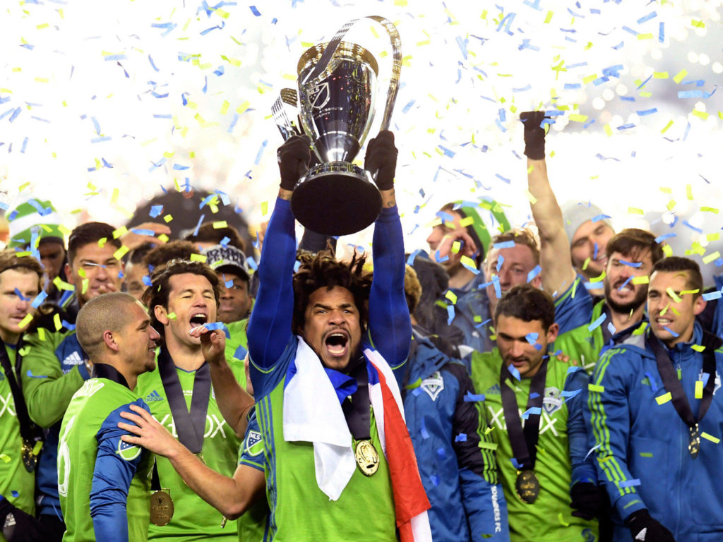 The Sounders' Roman Torres (center) hoists the trophy after winning the MLS Cup final over Toronto FC in 2016 in Toronto. (Frank Gunn/The Canadian Press via AP)