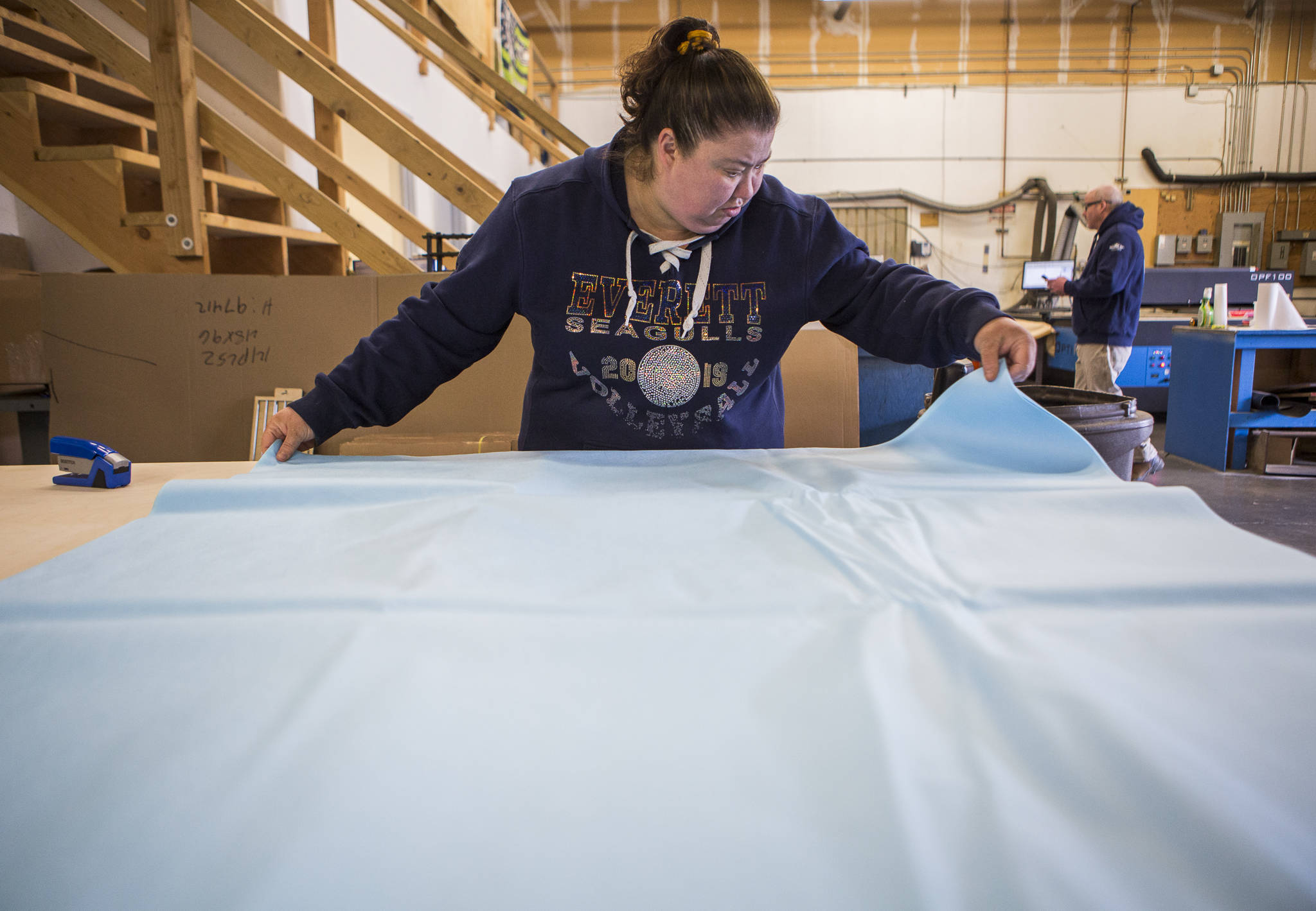 Tami Carrero lines up surgical wrap for face masks to be cut into straps and mask pieces Friday at Terrene Inc. in Mukilteo. The fabrication company specializes in laser work but modified operations to produce face masks for healthcare workers. (Olivia Vanni / The Herald)