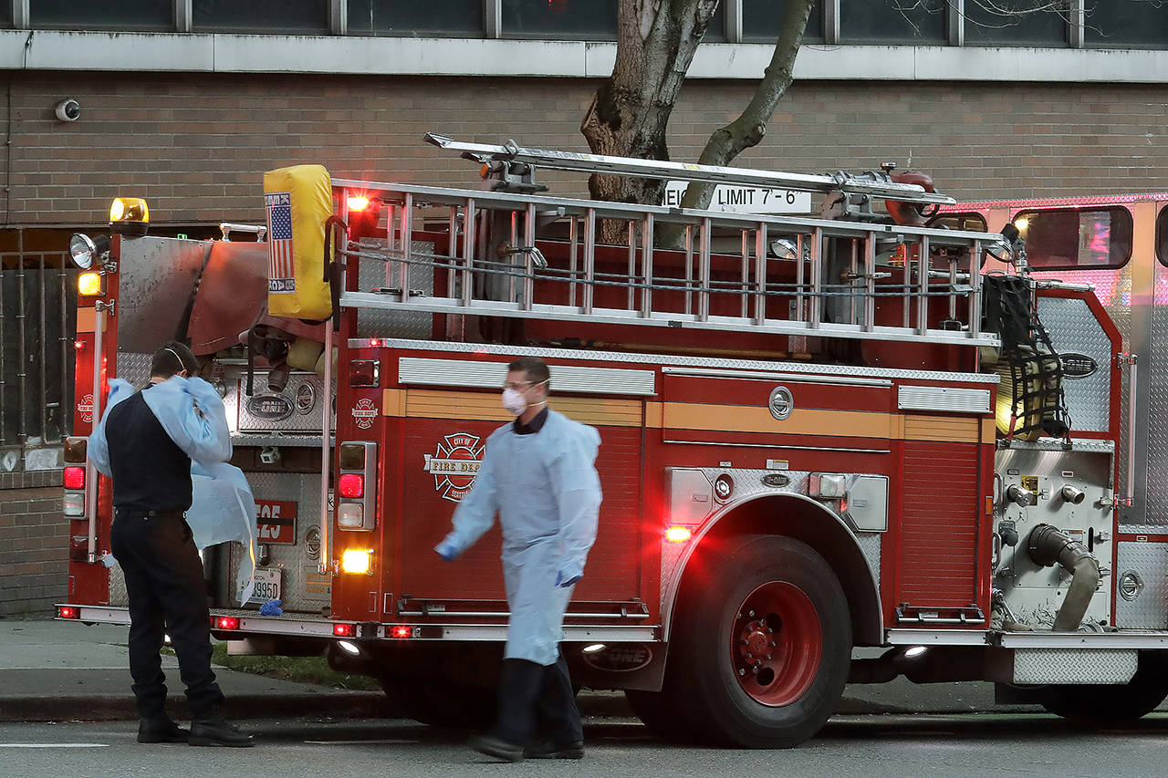 Seattle firefighters wearing masks, gowns, and gloves to protect against the transmission of the new coronavirus, walk and stand near their engine after responding to a medical call in Seattle on Tuesday. (AP Photo/Ted S. Warren)