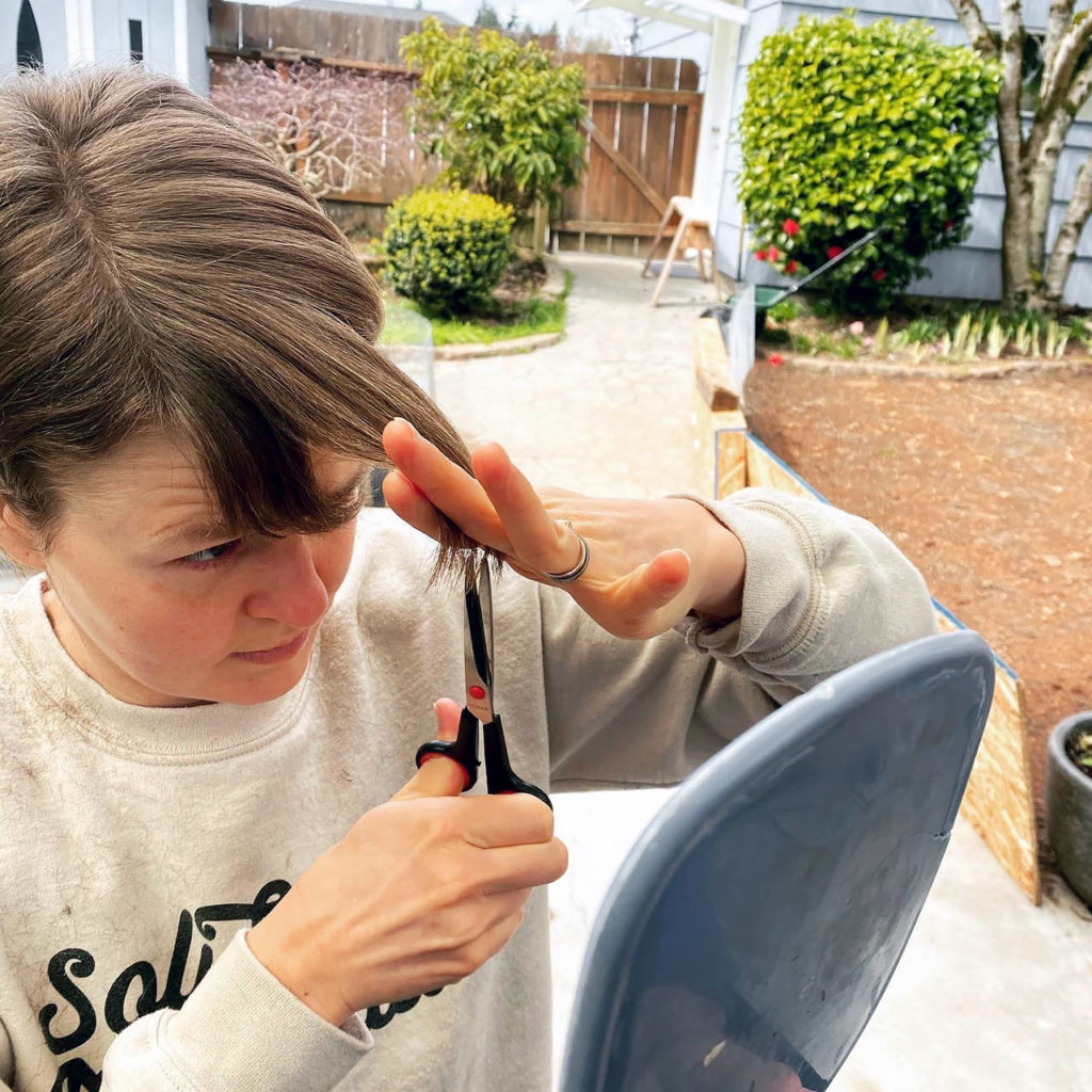 Emily Leopold trims her bangs, an increasingly common beauty routine with hair salons closed because of the coronavirus pandemic and Gov. Jay Inslee's emergency orders. (Courtesy of Al Leopold)