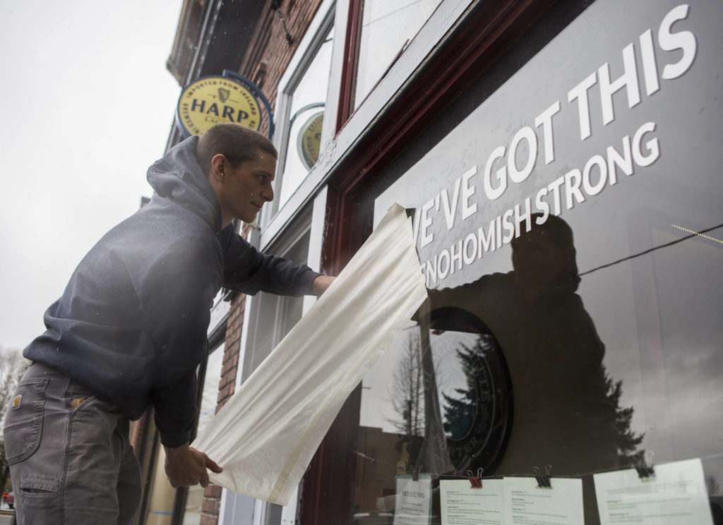 "Ethan Spain finishes putting a temporary vinyl on Fred's Rivertown Ale House window with the phrase, ""we've got this #snohomishstrong"" on Friday in Snohomish. (Olivia Vanni / The Herald)"
