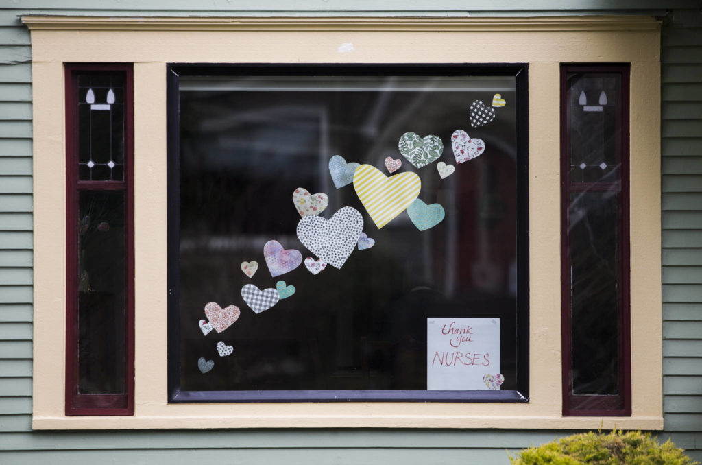 "Paper hearts and a sign that says, ""thank you nurses"" are affixed to in a window of a home on Rucker Avenue in Everett. (Olivia Vanni / The Herald)"