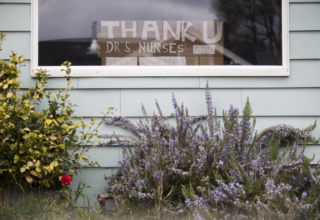 "A sign with the phrase, ""thank u dr's nurses and first responders"" sits on display in a window of a home along 15th Street on Friday in Everett. (Olivia Vanni / The Herald)"