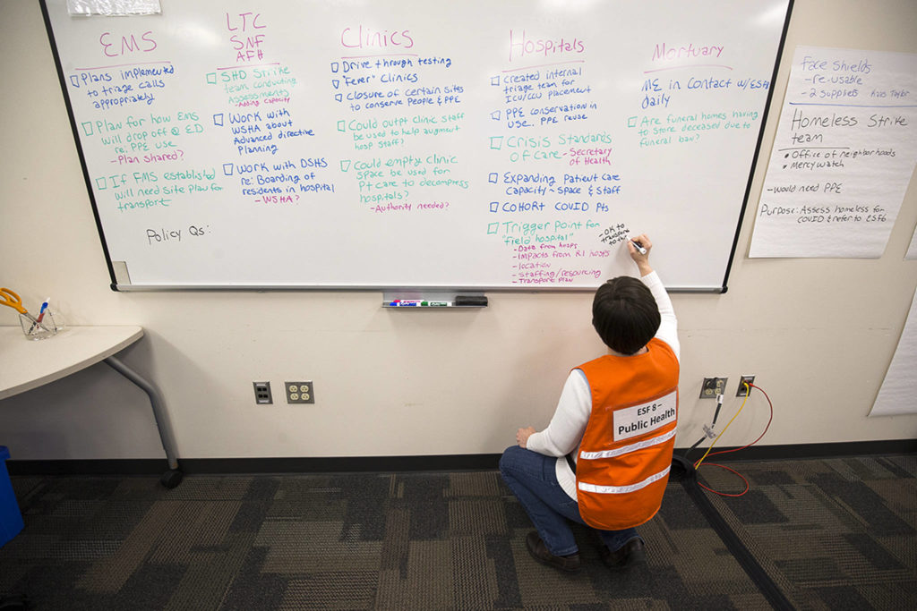 Assistant Director of Prevention Services Katie Curtis makes lists on a whiteboard in a room at the Snohomish County Emergency Management Center on March 30 in Everett. (Andy Bronson / The Herald)