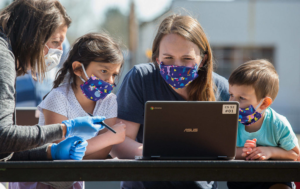 Jody Urban, left, helps Michelle Nunez setup a Chromebook at Frank Wagoner Elementary School as her daughter Lilah, left, and son Oilver watch. Students and their families picked up computers for online learning on Wednesday. (Andy Bronson / The Herald)
