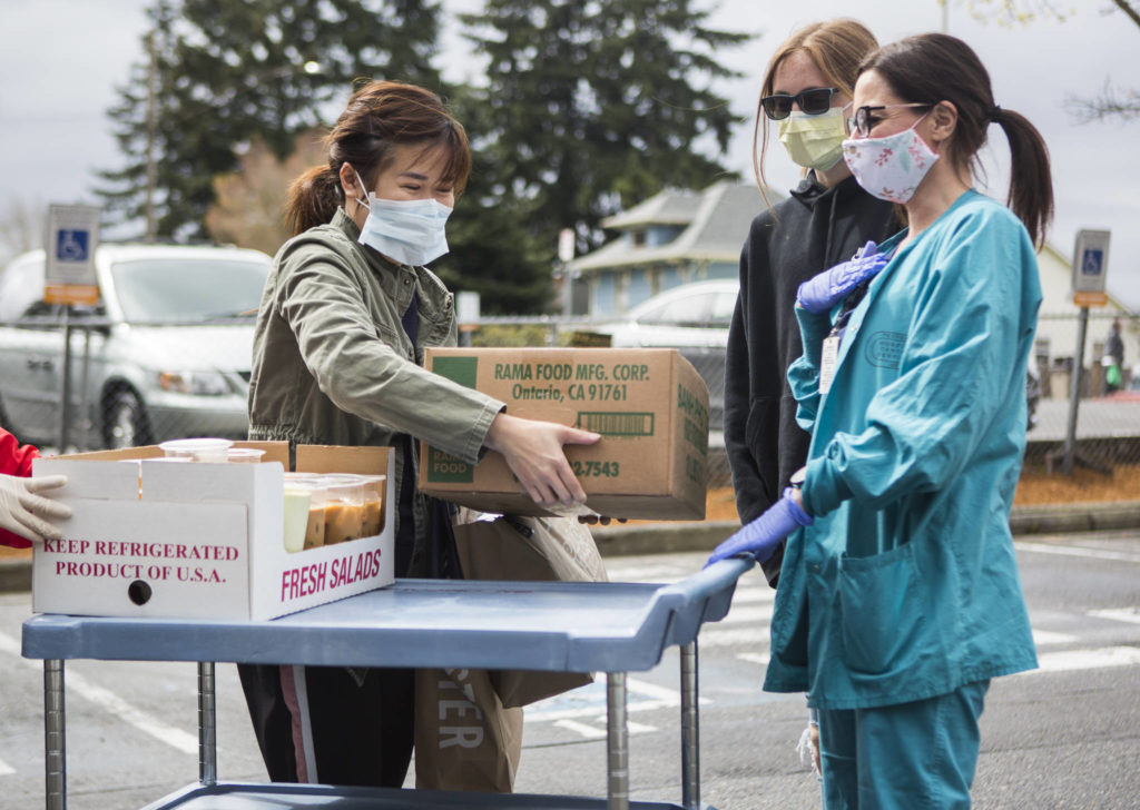 Pho Nguyen owner Cindy Nguyen (left) smiles behind her face mask as she delivers food on Saturday in Everett. (Olivia Vanni / The Herald)