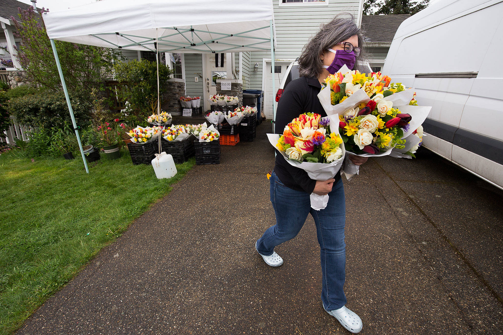 Gina Corpening carries off an armful of bouquets from Teng's Garden sold from the flower farm family's front porch in Everett. Teng's Garden and other flower vendors initially were prohibited from farmers markets because of public health restrictions, but now can sell after the state weighed in. (Andy Bronson / The Herald)