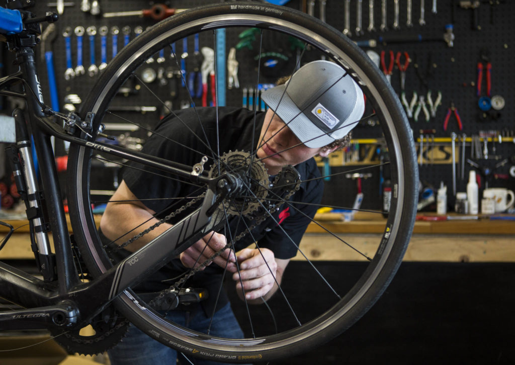 Bicycle Centres of Snohomish mechanic Nolan Sigurdson works on the wheel of a bike on April 18 in Snohomish. The Bicycle Centres have seen record numbers of people over the last few weeks as more people turn to bikes as a means of activity during the COVID-19 pandemic. (Olivia Vanni / The Herald)