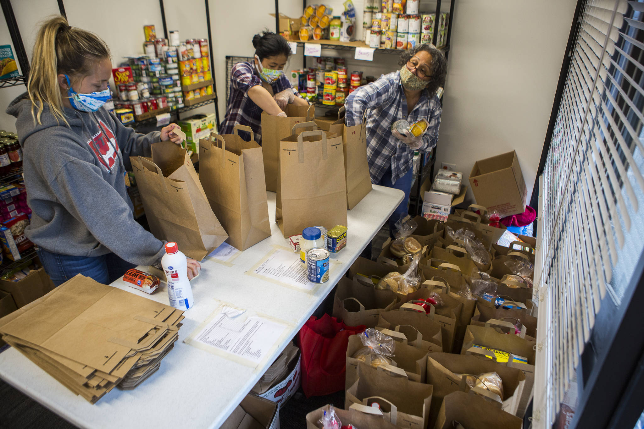 Taylor Eines (left), Akari Takayama (center) and Marilyn Robles (right) put together food bags for people to pick up at The Village on April 21 in Everett. (Olivia Vanni / The Herald)
