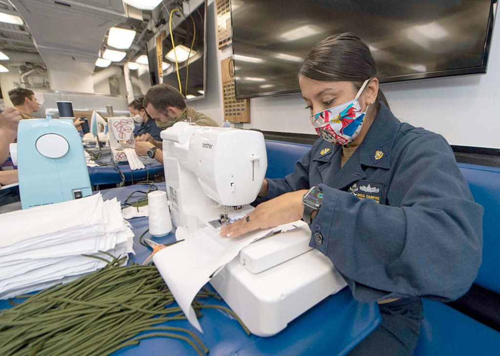 Chief Personnel Specialist Erica Campos, from Houston, assigned to the Everett-based guided-missile destroyer USS Kidd, sews fabric to make cloth face masks for the crew earlier this month while at sea. (Mass Communication Specialist 3rd Class Brandie Nuzzi / U.S. Navy)